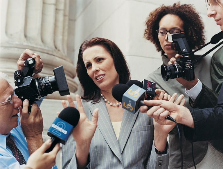 A photo of a woman surrounded by reporters with microphones and cameras.
