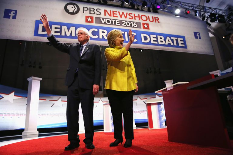 Hillary Clinton and Bernie Sanders wave to crowd at 2016 democratic presidential primary debate.