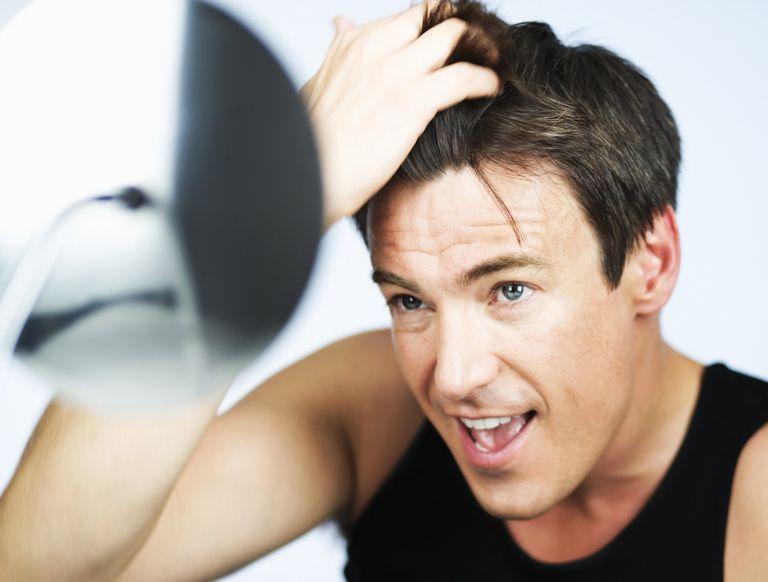 man combing finger through hair