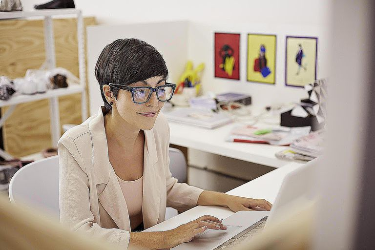 Creative businesswoman typing on laptop at...