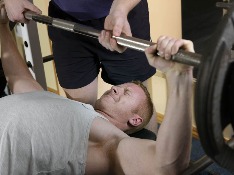 man doing chest press with spotter