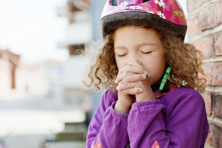 Niña usando casco de seguridad, rezando