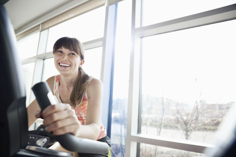 Woman exercising on stationary bike in fitness center