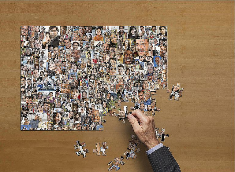 A man assembles a puzzle of faces, signaling the analytic work done by macro and micro sociologists.
