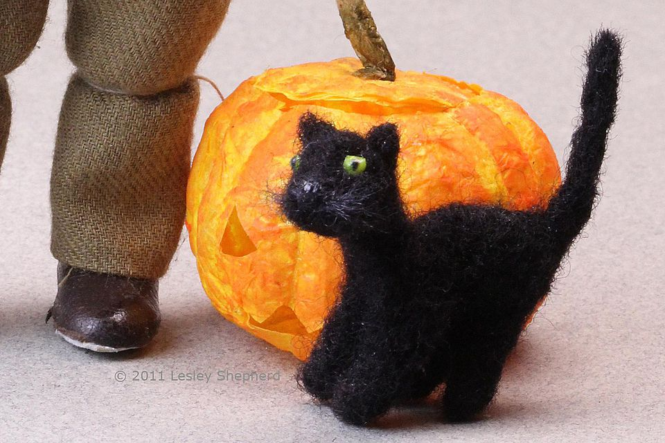 Poseable dollhouse scale needlefelt black cat stands beside a Halloween pumpkin
