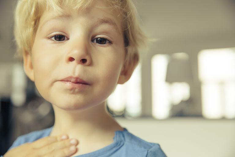 Portrait of little boy having sore throat