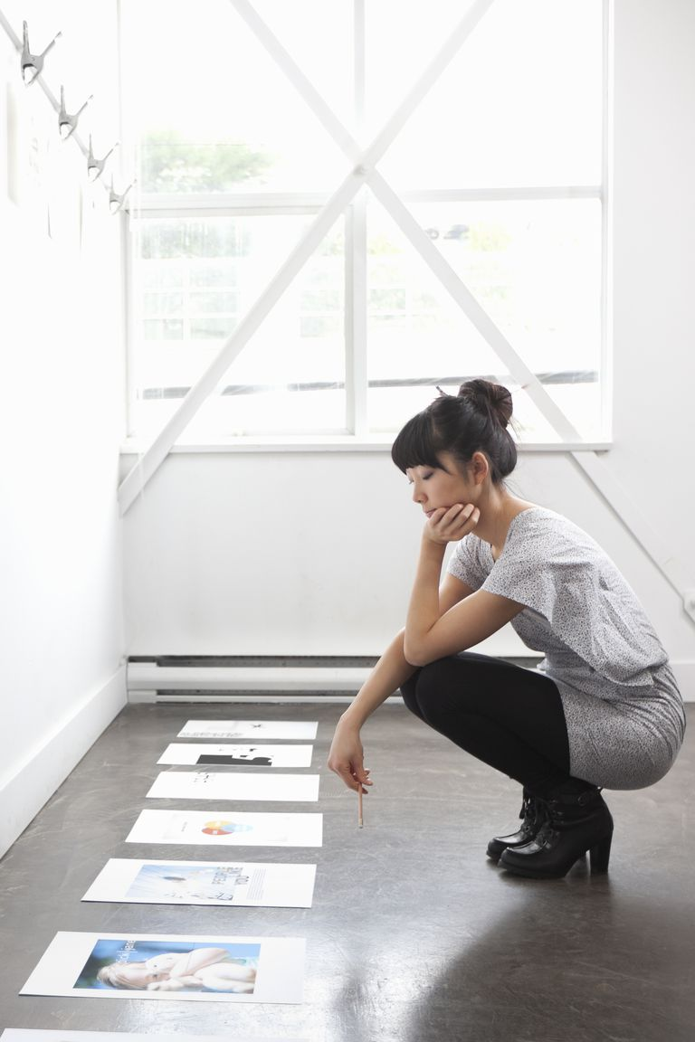 Young woman reviewing design mockups on floor