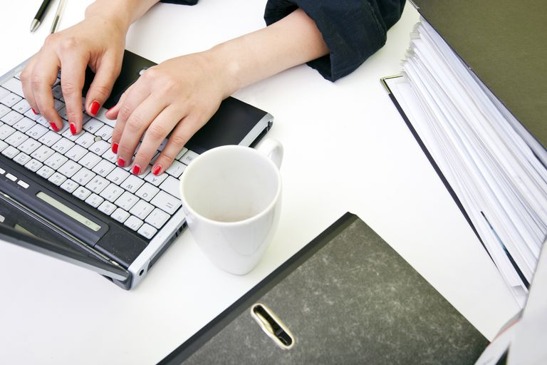 Close up of womans hands typing on laptop with folders and mug