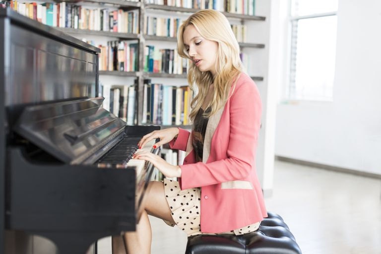 young stylish woman playing the piano