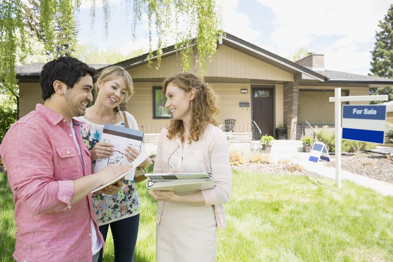 Realtor showing couple paperwork outside house