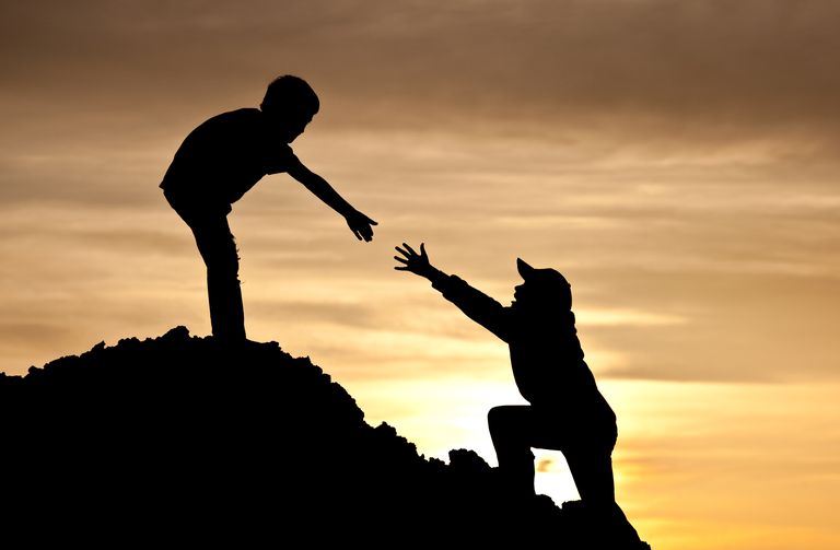 silhouette of a child helping another child up a hill