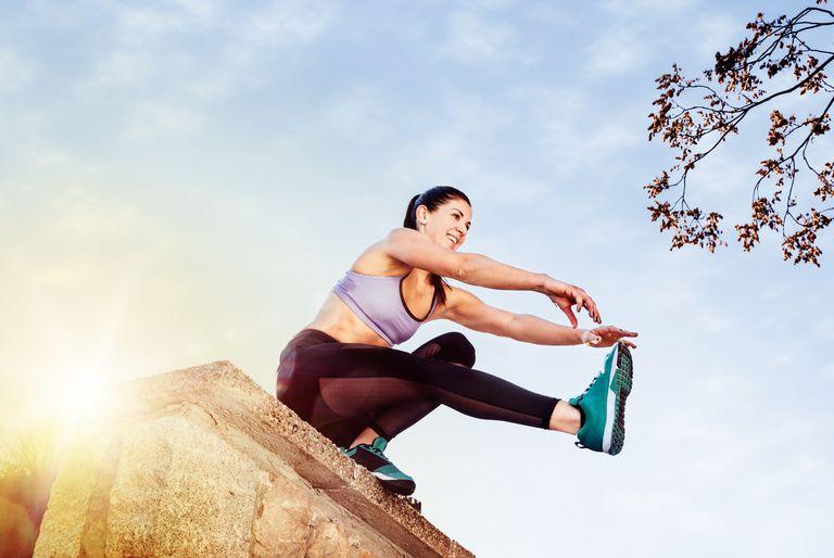 Woman doing single leg squat on a half wall