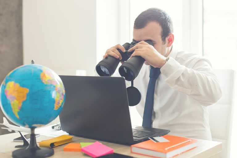 man checking computer with binoculars