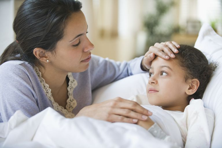 Sick girl in bed comforted by mother
