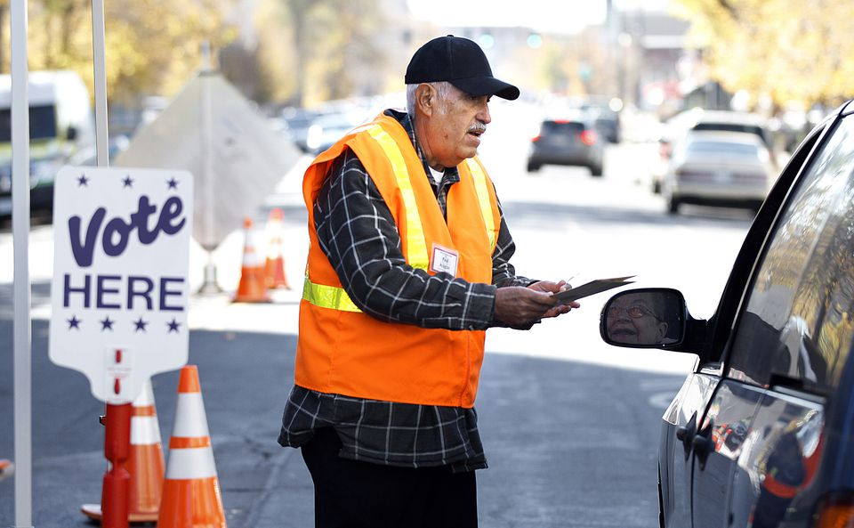 Denver County election judge Paul Aragon collects ballots from a passing motorist outside the Denver Elections Division building during the 2012 elections.