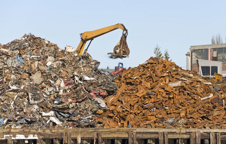 Crane moving scrap metal onto pile