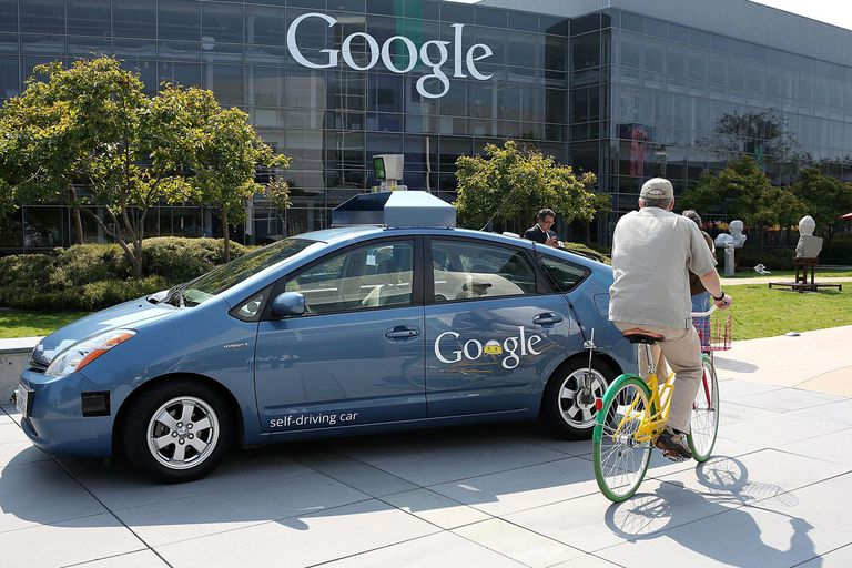 MOUNTAIN VIEW, CA - SEPTEMBER 25: A bicyclist rides by a Google self-driving car at the Google headquarters on September 25, 2012 in Mountain View, California.
