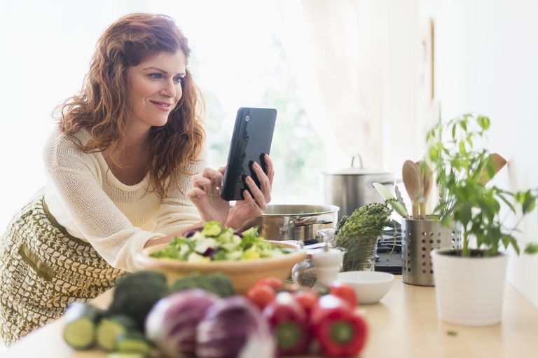 Woman using iPad in kitchen