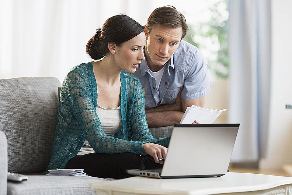 Couple looking at bills and their laptop