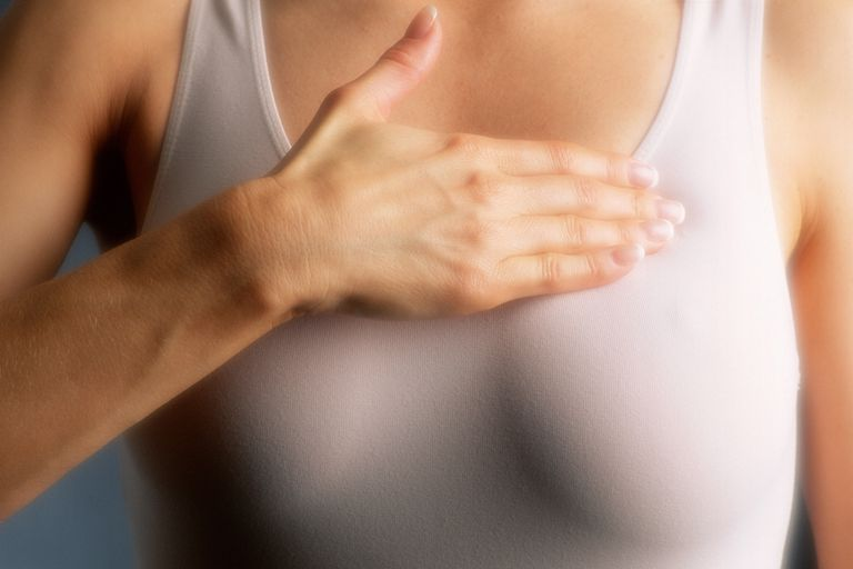 woman holding her hand above her breast palpating
