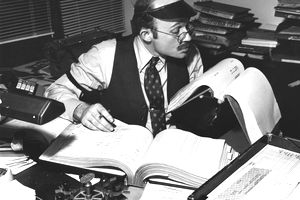 Black and white image of an accountant at a desk scrutinizing paper records
