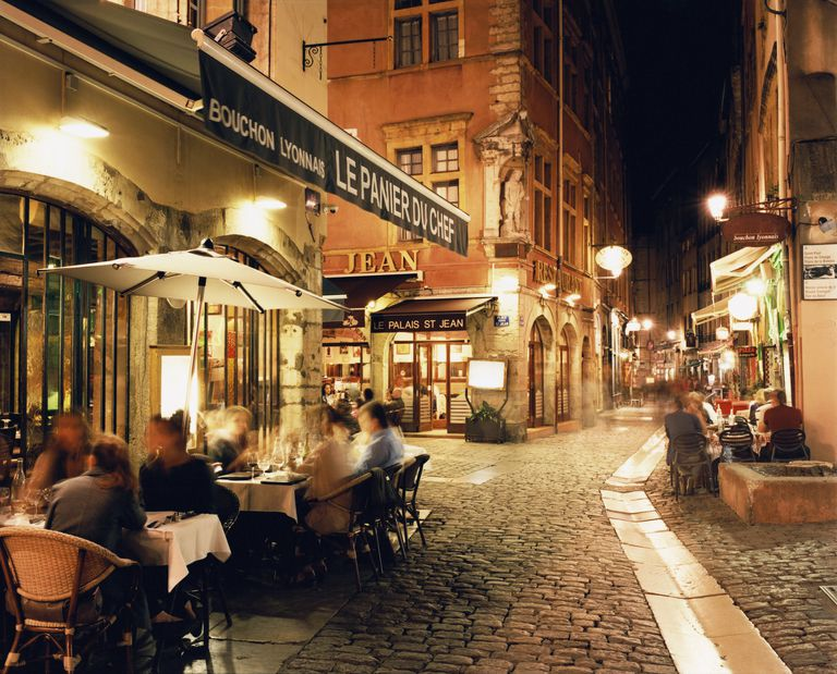 Lyon, People dining along cobbled street at night