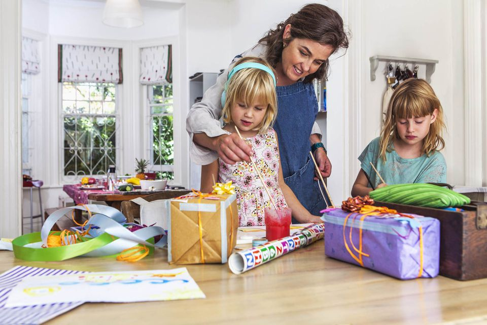 A picture of a family painting and wrapping gifts