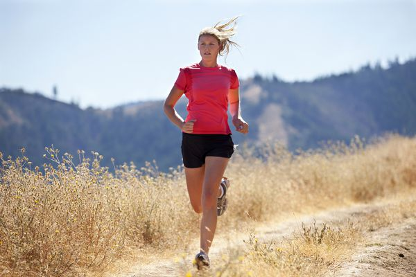 Woman running down trail with dried out wildflowers along the side of the path