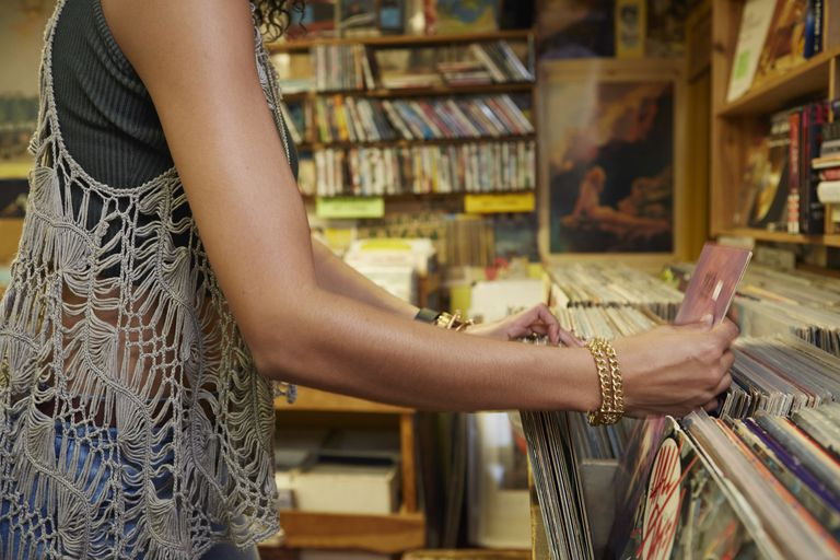 woman looking through records at record store