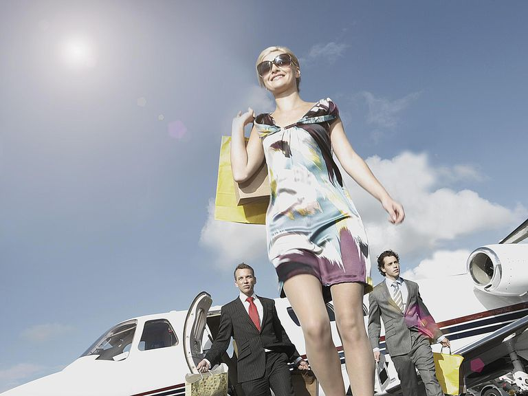 A woman exits a private jet, signaling high status in society.