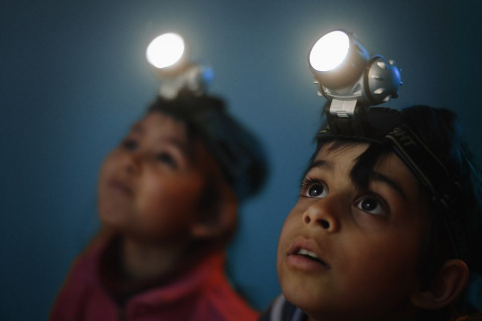 A picture of kids with flashlights on their heads