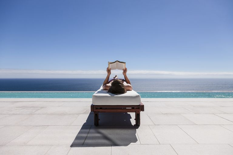 Woman reading on lounge chair at poolside overlooking ocean