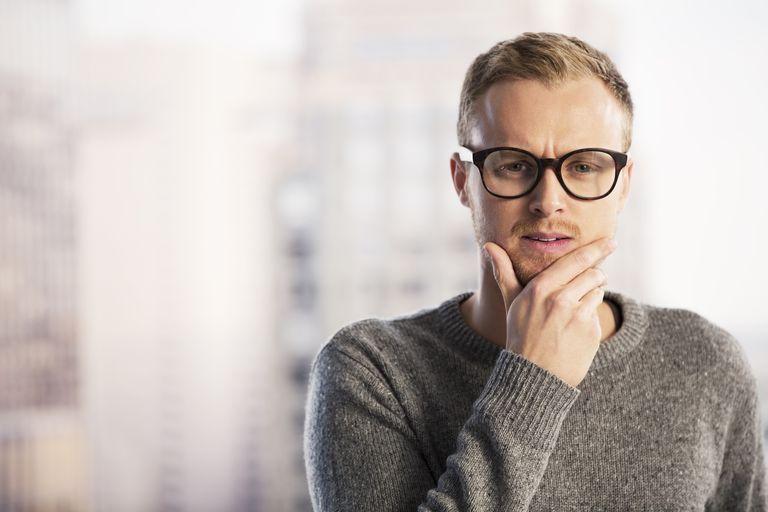 Pensive businessman with hand on chin