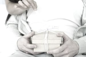 Man holding gift, woman's arm reaching around to untie the ribbon, cropped view