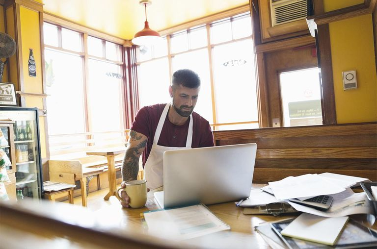 Male deli owner working on laptop