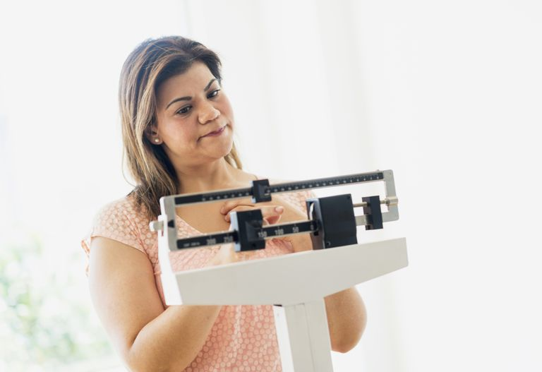 disappointed woman weighing herself on scale