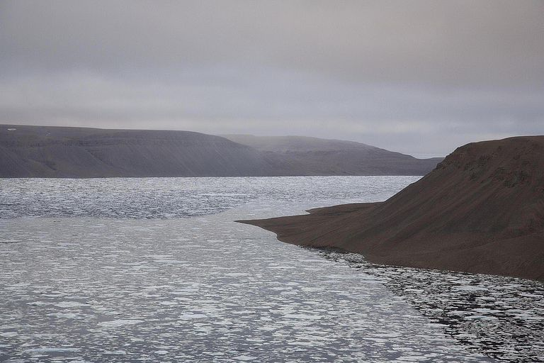Sea with ice and cliffs - elevated view of ocean inlet on the coast of Devon Island, Nunavut, Canada, looking out to the Northwest Passage