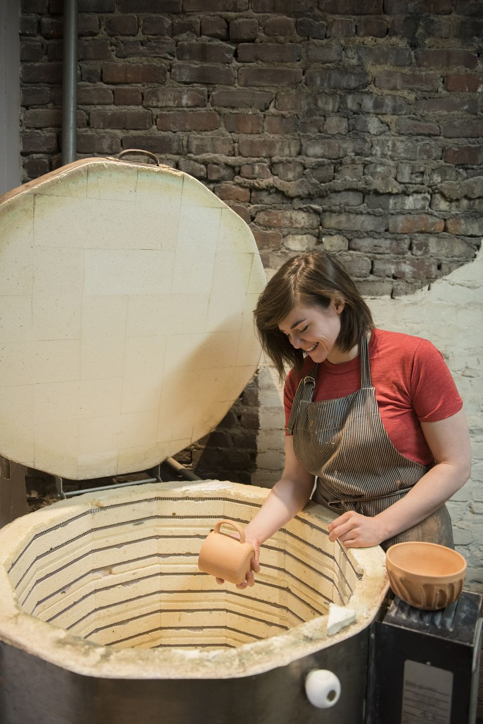 A woman putting clay in a kiln.