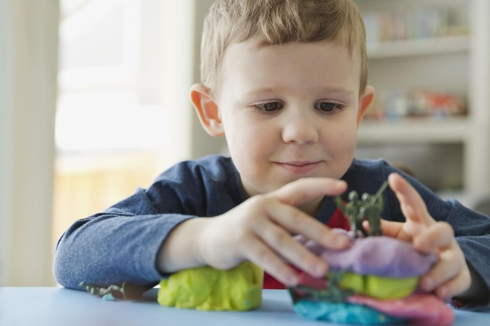 Boy playing with play dough at home