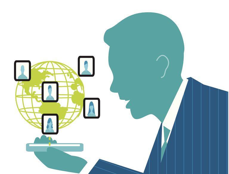 Businessman networking with co-workers on cell phone