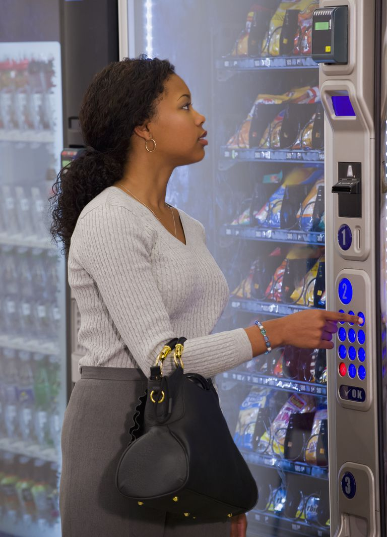 Mixed race woman buying snack from vending machine