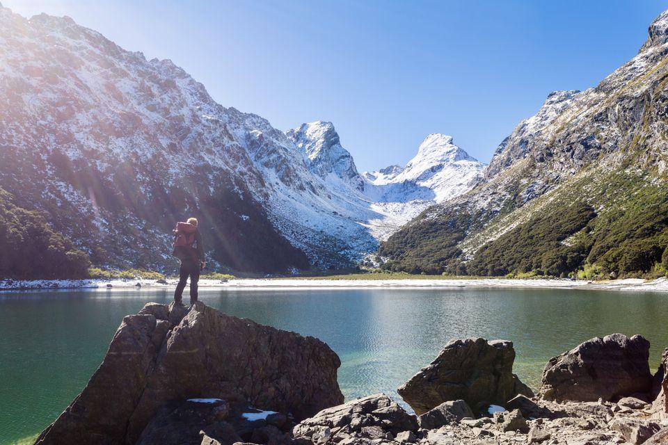 Hiker standing on a rock near lake Mackenzie, Fiordland National Park, Southland, New Zealand