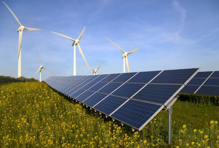 Solar panels and wind turbines in field