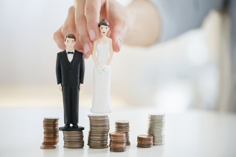Mixed race woman balancing bride and groom statues on coin stacks