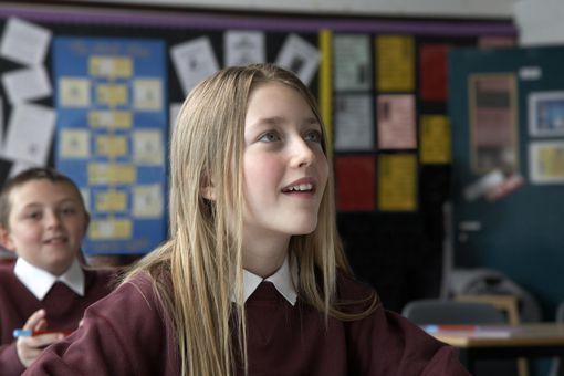 Schoolgirl (9-11) in classroom, schoolboy (8-10) in background