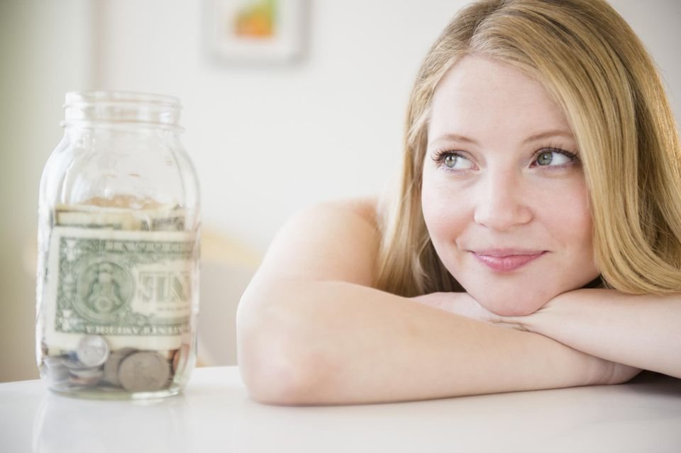 Woman With Jar Of Money Looking Away In Thought