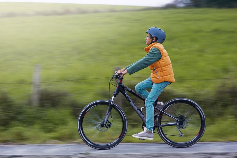 Boy with helmet cycling on his bike on footpath