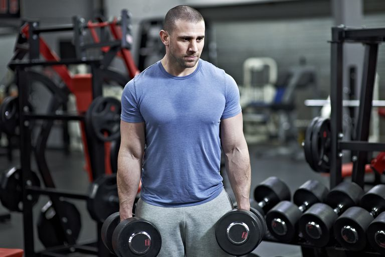 Man holding dumbbells in a gym.