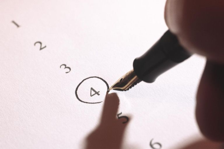 Man filling in questionnaire, close-up of hand