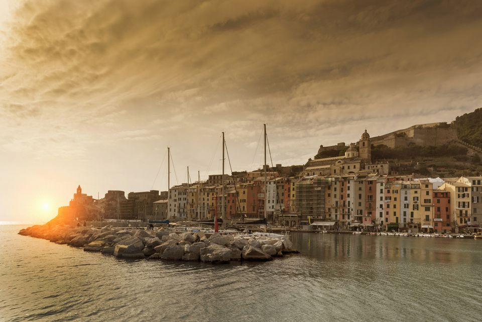 View of harbour and Church of St Peter on headland at sunset, Porto Venere, Liguria, Italy